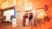A screen grab of a woman and two young people entering a large beige building.